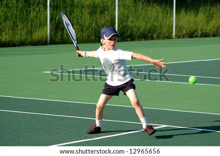 boy hitting forehand in tennis - stock photo
