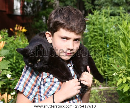 boy hold black cat as a collar on the summer garden background - stock photo