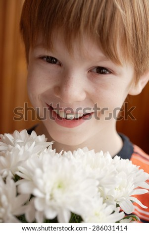 boy holding a bouquet of chrysanthemums, smiling and looking at the camera - stock photo