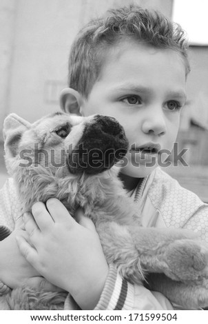 Boy holding a favorite stuffed toy dog shepherd..black and white photo. - stock photo
