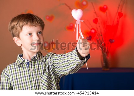 Boy holding a heart in his hands portrait - stock photo