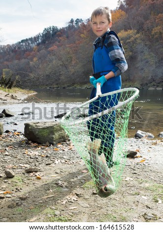 Boy holding a landing net freshly caught trout - stock photo