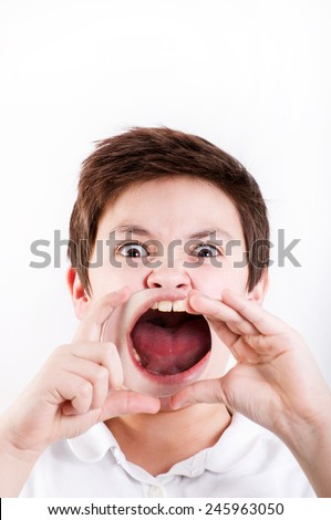 boy holding a magnifying glass to his mouth - stock photo