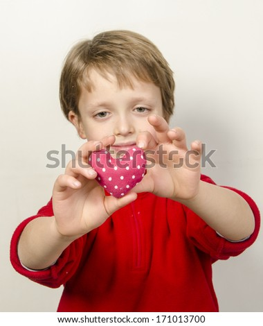 Boy holding a red heart for Valentines Day - isolated