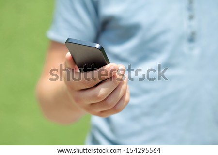 boy holding a touch phone against a green wall - stock photo