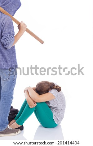 Boy holding a wooden stick to beaten on a little girl, isolated on a white background - stock photo