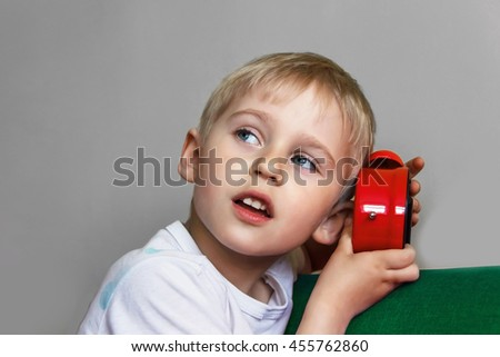 boy holding an alarm clock, a child and time red, concept of time, focus on the alarm clock, soft focus