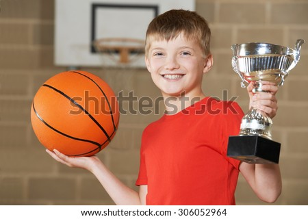 Boy Holding Basketball And Trophy In School Gymnasium - stock photo