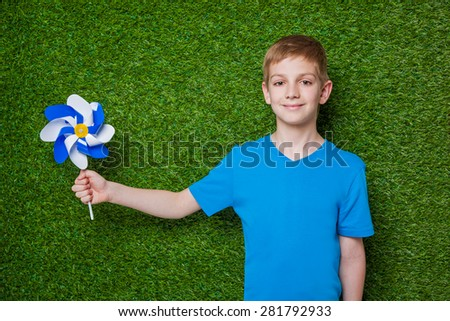 Boy holding blue white pinwheel over green grass