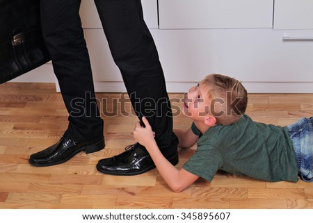 Boy holding dad's leg as he tries to leave for work. Child trying to stop father to go to work. Kid needs parent attention. Busy businessman father. Balance between work and time spent with family