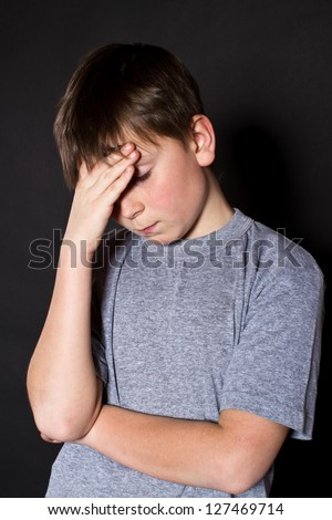 boy holding his head on a black background - stock photo
