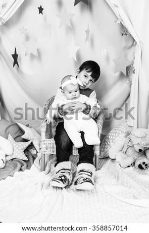 Boy holding his newborn baby sister - stock photo