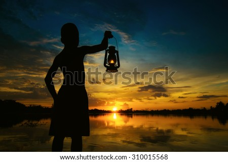 Boy holding Lamp looking for sunset . Abstract meaning hope of life. - stock photo