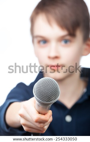Boy holding microphone, fucus on mic - stock photo