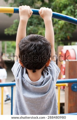 Boy holding on blue and yellow bar - stock photo