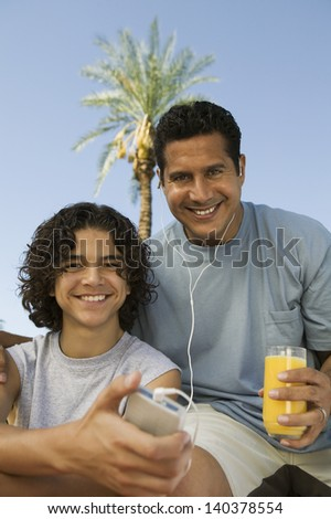 Boy (13-15) holding portable music player father listening with earphones an holding glass of juice front view portrait. - stock photo