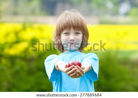 Boy Holding Red Apple in the Garden Smiling - stock photo
