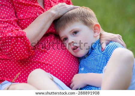 Boy holding the pregnant belly of his mother - stock photo