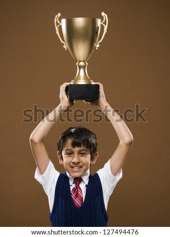 Boy holding trophy cup over his head and smiling