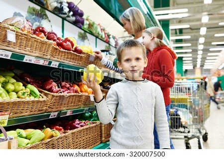 Boy holds yellow bell pepper in supermarket - stock photo