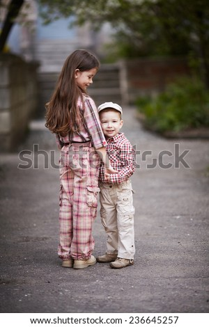 boy hugging cute sister and looks up