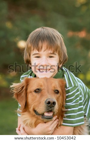 Boy Hugging Golden Retriever - stock photo