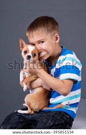 boy hugging his little dog - stock photo