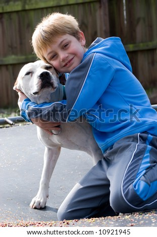 Boy hugging his pit bull dog - stock photo