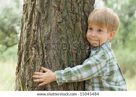 boy hugs a tree in forest - child care ecology environment nature