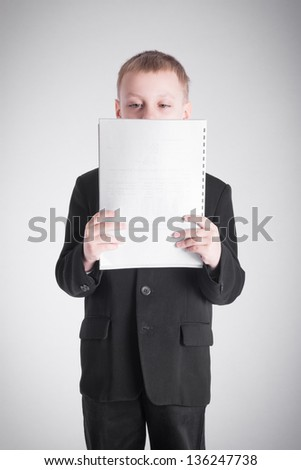 Boy in a black suit looking at a stack of paper
