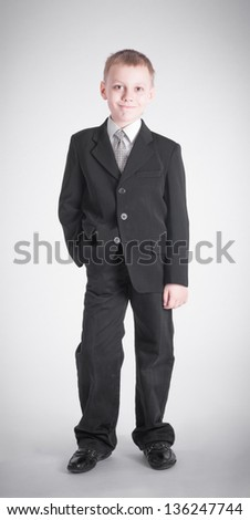 Boy in a black suit on gray background