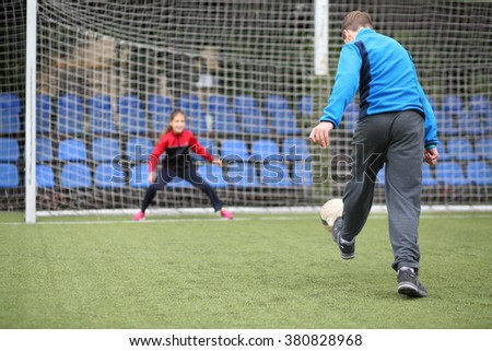 Boy in a blue tracksuit throws the ball into the goal with girl keeper - stock photo