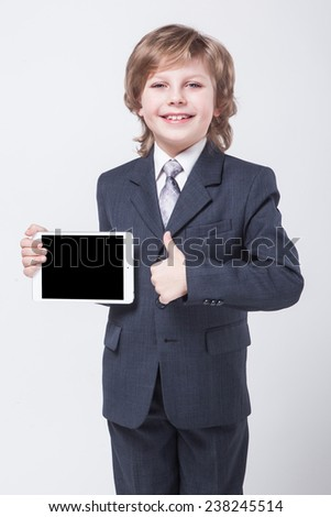 Boy in a business suit and tie holding a tablet, the best deal - stock photo