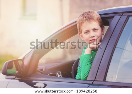 Boy in a car smiling - stock photo