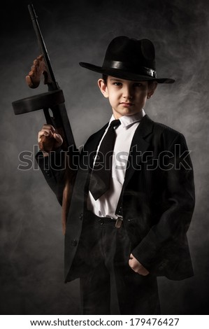 Boy in a gangster with a gun on a black background