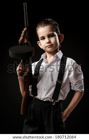 Boy in a gangster with a gun on a black background - stock photo