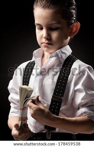 Boy in a gangster with money on a black background