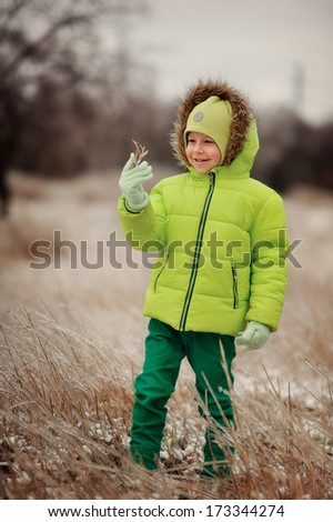 boy in a green suit walks in the park in winter with frozen trees and grass
