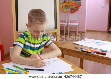 boy in a green T-shirt draws a picture