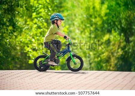 boy in a helmet riding bike - stock photo