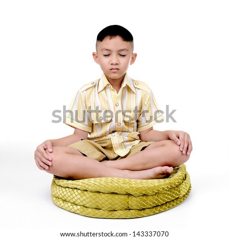 Boy in a lotus pose meditation and yoga - stock photo