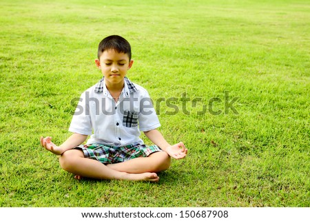 Boy in a lotus pose meditation and yoga on the grass in public p - stock photo