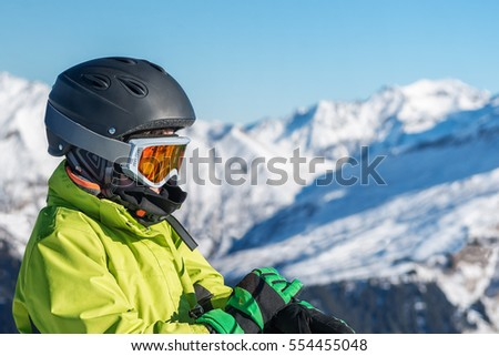 boy in a mountain-skiing helmet and goggles enjoying the beautiful view
