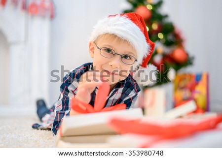 Boy in a red Christmas hat lying on the floor and opens his christmas gifts. - stock photo