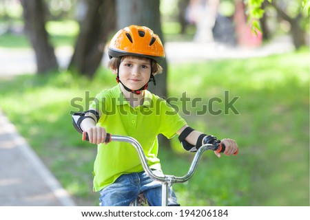 boy in a safety helmet rides a Bicycle on a Bicycle tracks - stock photo