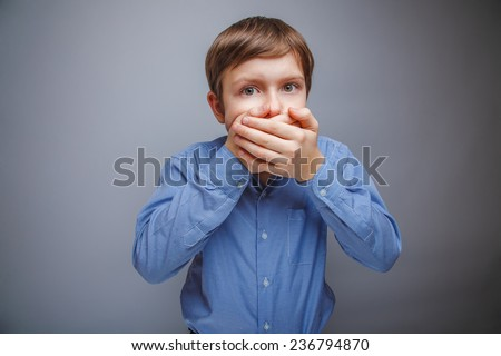 boy in a shirt covered with fright mouth with her hands - stock photo