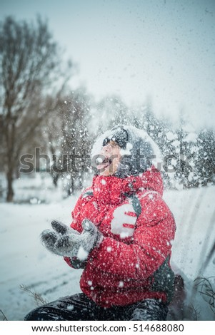 boy in a snowdrift sits and catches a snowflake mouth