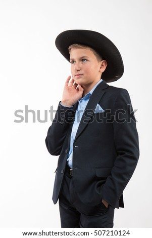 Boy in a suit and a black hat on a white background