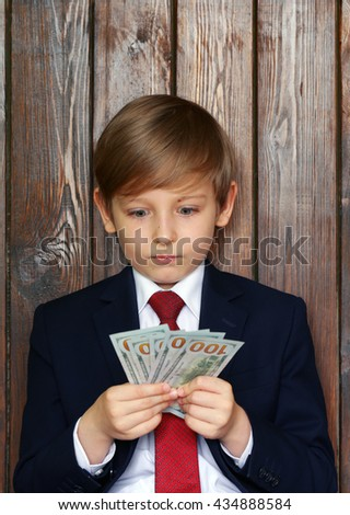 Boy in a suit with cash dollars - business concept - stock photo
