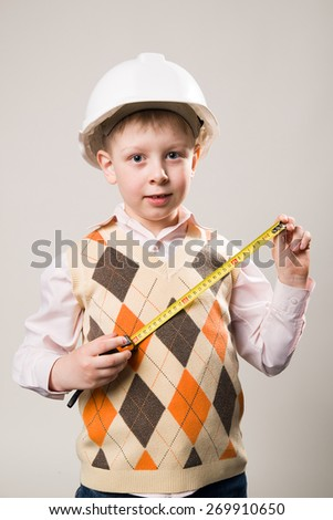 Boy in a white construction helmet and a tape measure in hand - stock photo